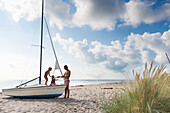 Father and two children (1-4 years) playing on a sailboat at Baltic Sea beach, Marielyst, Falster, Denmark