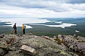 Two hikers on summit of mountain Kivakkatunturi, Paanajaervi National Park, Republic of Karelia, Russia