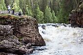 Three hikers near waterfall Kiutakoengaes waterfall, Oulanka National Park, Northern Ostrobothnia, Finland