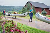 A woman and a boy transporting a canoe to lake Glafsfjorden, Vaermeln, Vaermland, Sweden