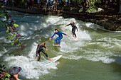 Surfers on the Eisbach river in the English Gardens, Munich, Upper Bavaria, Bavaria, Germany