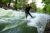 Surfer surfing on the Eisbach in the English Garden, Munich, Upper Bavaria, Bavaria, Germany