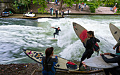 Surfers surfing on the Eisbach in the English Garden, Munich, Upper Bavaria, Bavaria, Germany