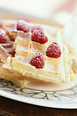 Waffles topped with raspberries and powdered sugar