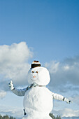 Person sticking arms out from behind snowman
