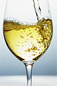 White wine being poured into wine glass, close-up