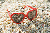 Heart-shaped sunglasses on beach