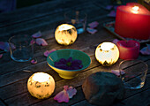 Candles glowing on table decorated with rose petals, and bowl holding floating flower