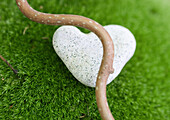 Smooth branch and heart shaped stone on moss