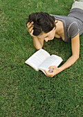 Woman lying in grass, reading book