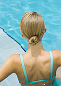 Young woman standing in pool, rear view, head and shoulders