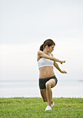 Young woman doing stretching exercises by lakeside