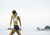 Young woman working out with weights by lakeside