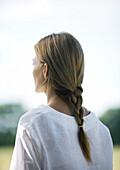Woman outdoors, hair braided, rear view