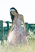 Young woman in dress walking through field