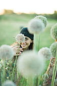 Young woman hiding behind allium flower, looking at camera