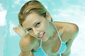 Woman in pool, smiling at camera, high angle view