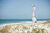 Young woman doing handstand in dunes, ocean in background