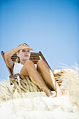 Young woman sitting in deck chair, in dunes, shading eyes with hand