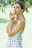 Woman holding apple up to mouth, looking at camera