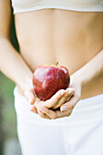 Woman holding apple in front of bare abdomen, close-up of mid section