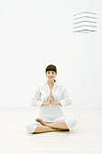 Woman sitting in lotus position on floor, smiling at camera