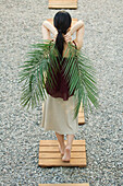 Woman walking on footpath, holding palm leaves behind back