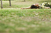 Woman lying on grass, daydreaming