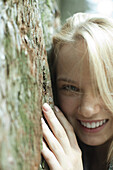 Smiling young woman leaning against tree trunk, cropped