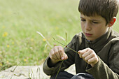 Boy sitting in grass, watching ladybug crawling on twig