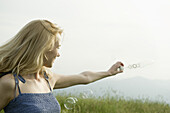 Young woman holding out bubble wand in wind