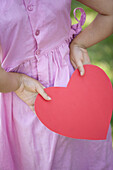 Girl holding paper heart behind back, cropped