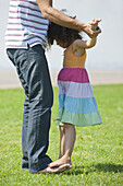 Girl standing on father's feet