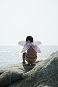 Girl wearing butterfly costume, crouching on rock and looking at ocean
