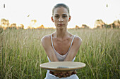 Young woman holding out plate with stone