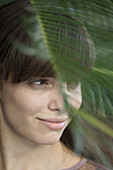 Young woman behind palm frond, looking away in thought