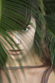 Young woman behind palm frond, portrait