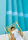 Woman reading in lounge chair next to pool