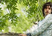 Young man in hammock, looking at camera