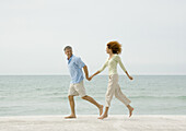 Mature couple running on beach