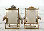 Couple sitting in beach chairs, holding hands, rear view