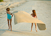 Two girls running on beach, holding blanket out in wind