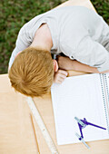 Boy with head on table next to open notebook