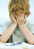 Boy covering face, homework on table in front of him