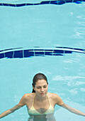 Woman standing in pool, eyes closed, front view