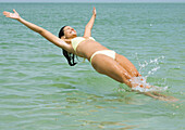 Woman jumping backwards into sea