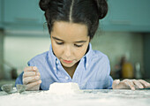 Girl standing at kitchen counter, looking down at mound of dough