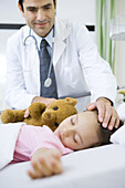 Doctor with hand on sleeping child's head, smiling