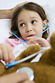 Child holding toy stethoscope to teddy bear, talking to man