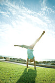 Girl doing cartwheel on grass